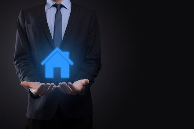 Immobilienkonzept, geschäftsmann, der eine hausikone hält. haus auf hand. eigentumsversicherungs- und sicherheitskonzept. schutzgeste des menschen und symbol des hauses.