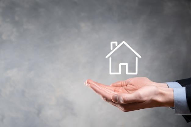 Immobilienkonzept, geschäftsmann, der eine hausikone hält. haus auf hand. eigentumsversicherungs- und sicherheitskonzept