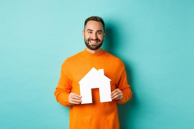 Immobilienkonzept. glücklicher junger mann, der nach wohnungsmiete sucht, hauspapier hält und lächelt und auf blauem hintergrund steht