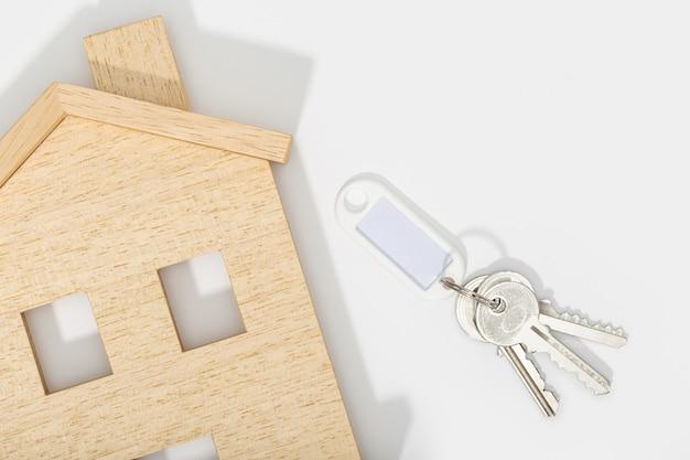 Immobilienkonzept. hausikone mit schlüsseln auf weißem hintergrund. attrappe, lehrmodell, simulation. speicherplatz kopieren. draufsicht