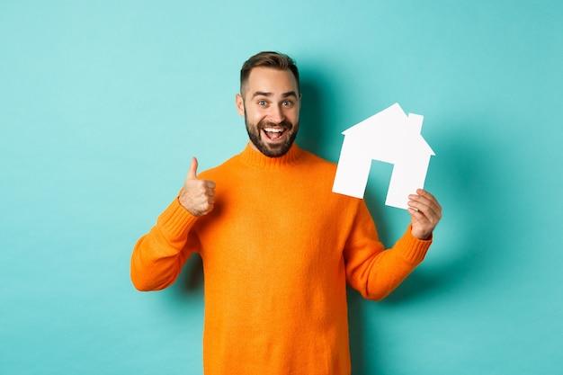 Immobilienkonzept. zufriedener mann, der agentur empfiehlt, daumen hoch und hausmarke zeigt, auf blauem hintergrund stehend.