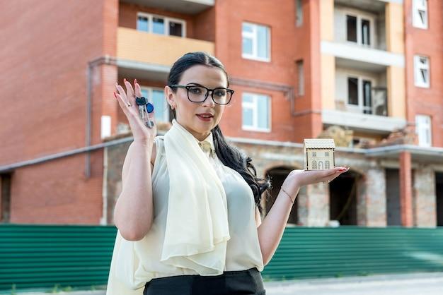 Immobilienkonzeption, frau, die schlüssel und hausmodell hält