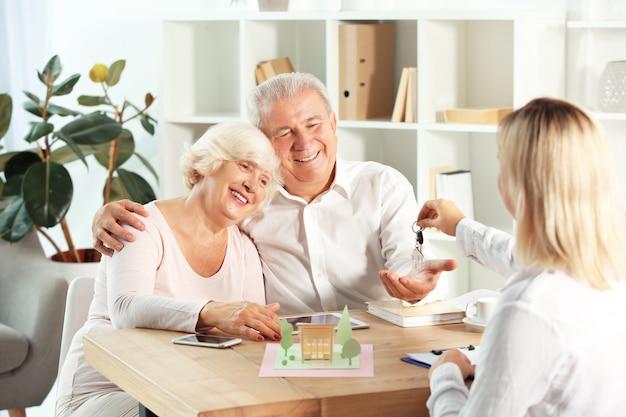 Immobilienmakler, der dem glücklichen reifen paar im büro den schlüssel vom neuen haus gibt