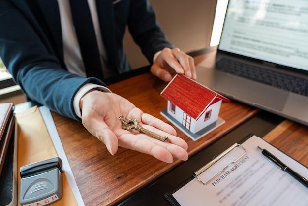 Immobilienmakler, der dem kunden den schlüssel gibt