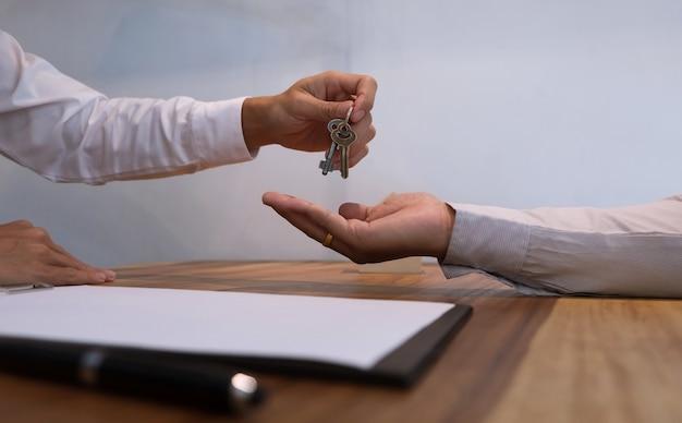 Immobilienmakler, der dem kunden nach vertragsunterzeichnung schlüssel gibt.