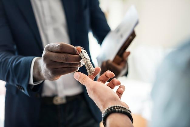 Immobilienmakler, der den hausschlüssel einem kunden übergibt