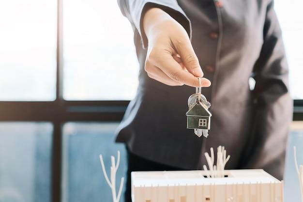 Immobilienmakler, der den hausschlüssel für den kunden übergibt