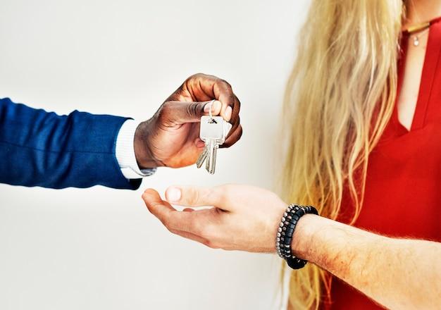 Immobilienmakler, der den kunden den hausschlüssel übergibt