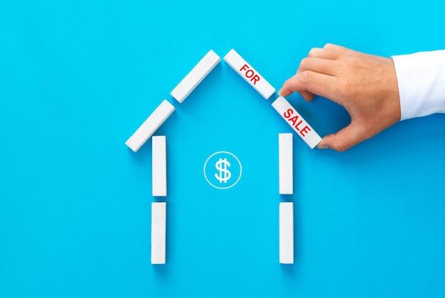 Immobilienmakler, der ein haus aus holzklötzen mit text zum verkauf baut.