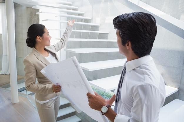 Immobilienmakler, der einem potenziellen käufer treppe zeigt