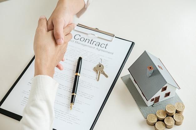 Immobilienmakler, der hände mit kunden für geschäftsvertrag rüttelt, um haus zu kaufen,
