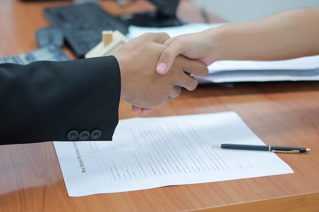 Immobilienmakler, der hände mit kunden nach zeichenhauptkredit-vertragsunterzeichnung rüttelt.