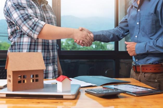 Immobilienmakler, der hände mit seinem kunden nachdem dichtungsabkommen rüttelt.