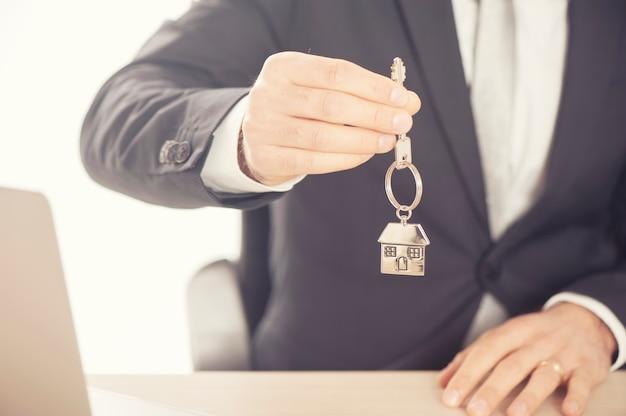 Immobilienmakler, der hausschlüssel an einem silbernen schlüsselbund in hausform gibt