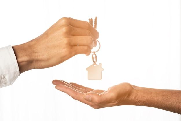 Immobilienmakler, der hausschlüssel gibt