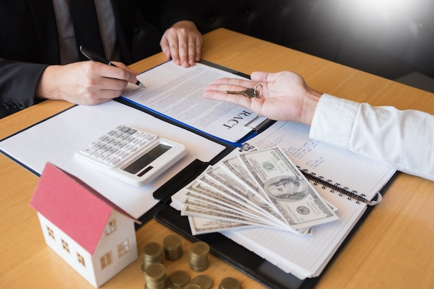Immobilienmakler, der hausschlüssel-kundenvereinbarungseigenschaft zum verkauf gibt
