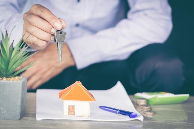 Immobilienmakler, der hausschlüssel überreicht