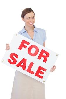 Immobilienmakler, der mit für verkaufszeichen aufwirft
