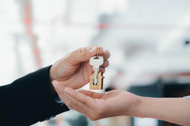 Immobilienmakler, der schlüssel mit hausförmigem schlüsselbund hält.