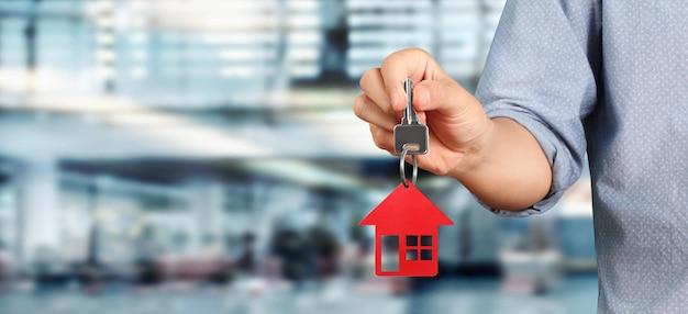 Immobilienmakler, der schlüssel mit winzigem rotem haus hält
