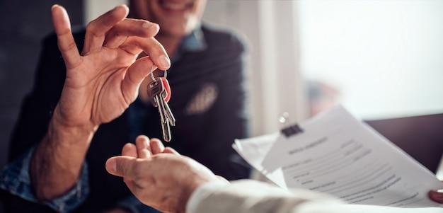 Immobilienmakler, der seinem kunden schlüssel übergibt