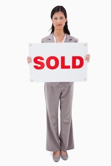 Immobilienmakler, der verkaufszeichen hält