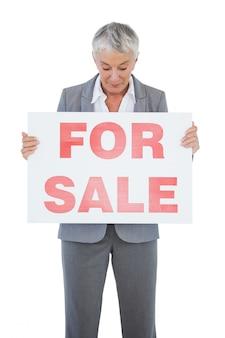 Immobilienmakler, der zeichen für verkauf hält und betrachtet