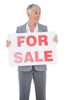 Immobilienmakler, der zeichen für verkauf hält und weg schaut