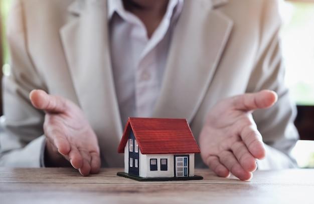 Immobilienmakler gibt musterhaus zur vereinbarung mit kunden, um versicherungsvertrag zu unterzeichnen