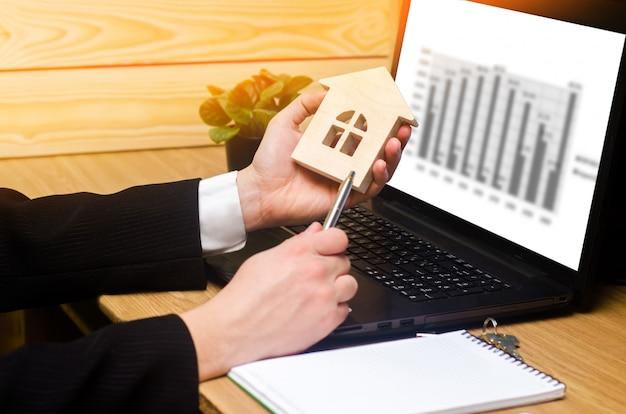 Immobilienmakler hält ein hausmodell, zeichen füllt dokumente, die hinter laptop sitzen