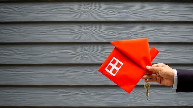 Immobilienmakler holding haus und schlüssel