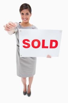 Immobilienmakler mit dem verkaufenden zeichen, das schlüssel überreicht