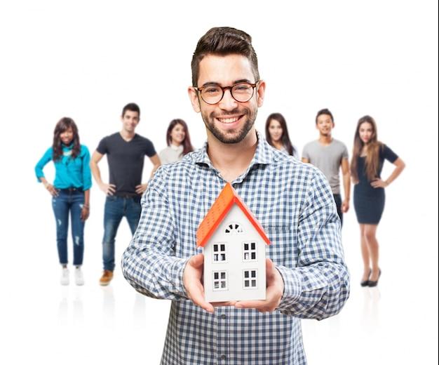 Immobilienmakler mit einem modell zu hause