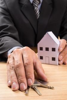 Immobilienmakler mit hausmodell und schlüssel
