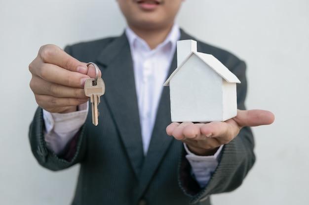 Immobilienmakler mit hausmodell und schlüsseln