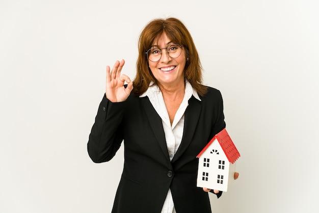 Immobilienmakler mittleren alters, der ein hausmodell hält, isoliert fröhlich und zuversichtlich zeigt ok geste.
