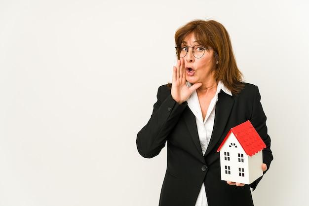 Immobilienmakler mittleren alters, der ein hausmodell isoliert hält, sagt eine geheime heiße bremsnachricht und schaut zur seite