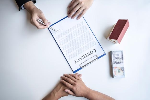 Immobilienmakler präsentieren wohnungsbaudarlehen und geben dem kunden nach unterzeichnung des kaufvertrags schlüssel