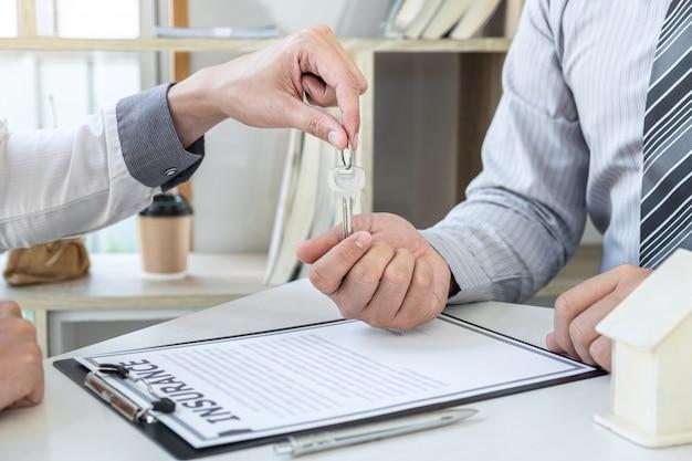 Immobilienmakler präsentieren wohnungsbaudarlehen und senden schlüssel an kunden nach vertragsunterzeichnung