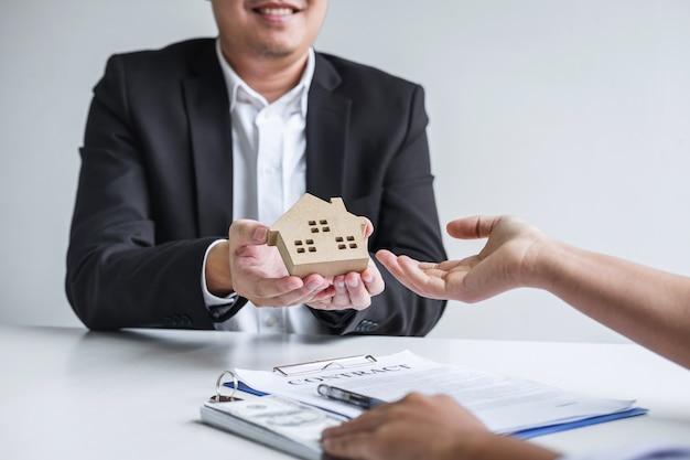 Immobilienmakler sendet hausmodell an den kunden nach unterzeichnung des vertragsvertrags immobilien mit genehmigtem hypothekenantragsformular
