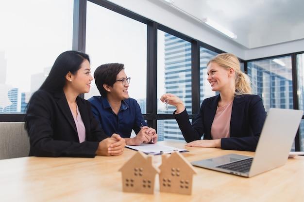 Immobilienmakler treffen asiatisches paar, um wohneigentum, lebensversicherung und hausinvestition anzubieten
