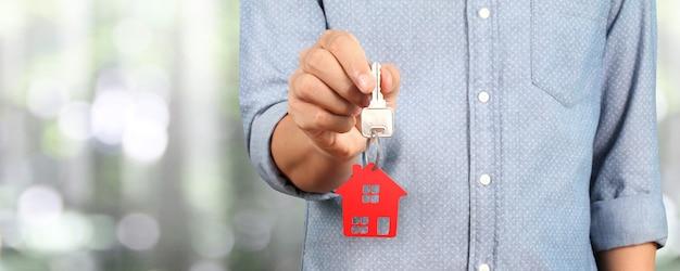 Immobilienmakler übergeben einen hausschlüssel in der hand