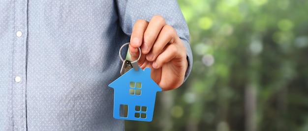 Immobilienmakler übergeben hausschlüssel in der hand