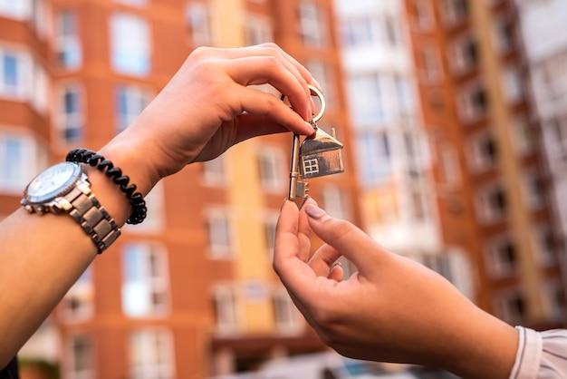 Immobilienmakler übergibt hausschlüssel für den neuen eigentümer zu hause. verkauf oder miete nach hause