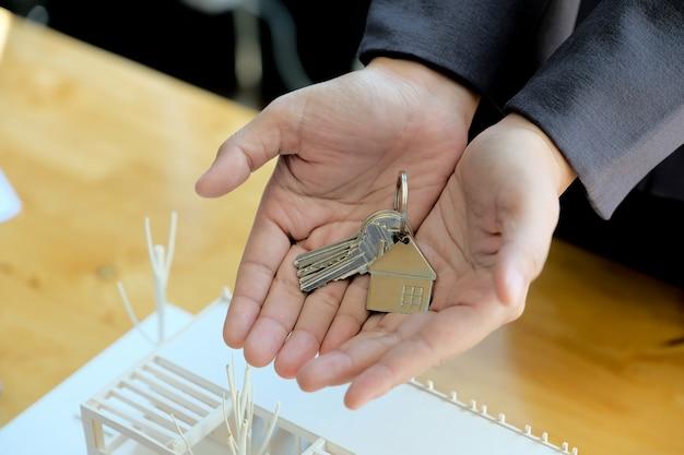 Immobilienmakler übergibt hausschlüssel mit genehmigtem hypothekenantragsformular und bietet handschlag an
