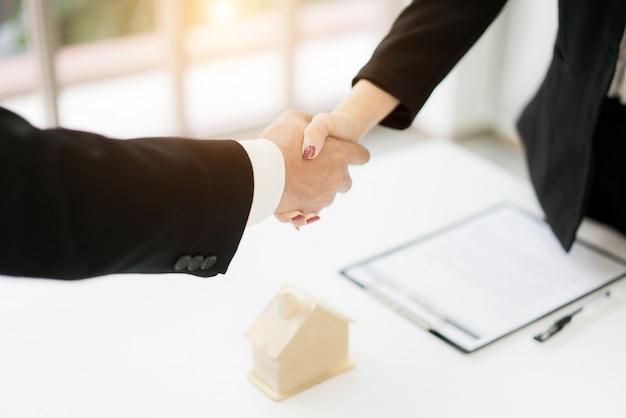 Immobilienmakler und kunde, die hände rütteln, nachdem ein vertrag unterzeichnet wurde
