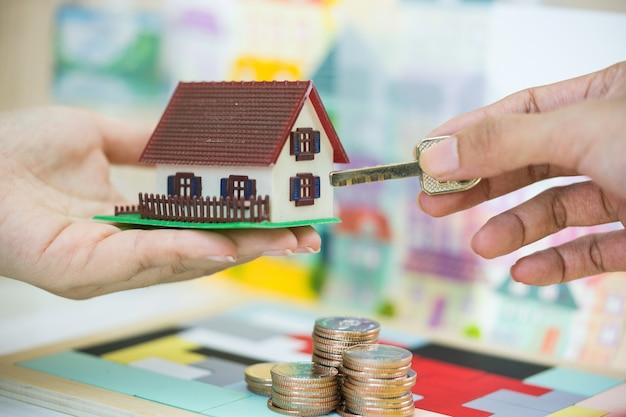 Immobilienmakler und kunde, die hausmodell und schlüssel in den händen austauschen.