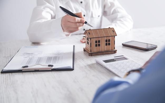 Immobilienmakler zeigt dem neuen käufer das hausmodell.