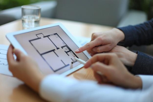 Immobilienmakler zeigt hauspläne auf elektronischem tablet