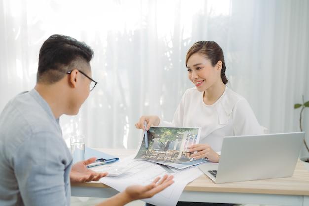 Immobilienmakler zeigt hauspläne für kunden im büro.